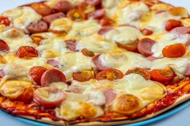 Frisch zubereitete leckere hausgemachte pizza mit tomaten kirsche, würstchen und käse hautnah.