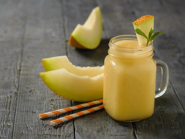 Frisch zubereitete melonen-, orangen- und bananen-smoothies und drei scheiben melone auf einem dunklen holztisch.