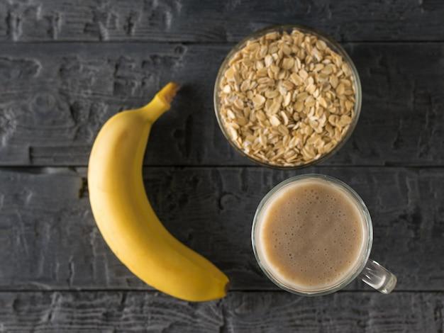 Frisch zubereiteter bananen-smoothie, banane und schüssel haferflocken auf dem tisch