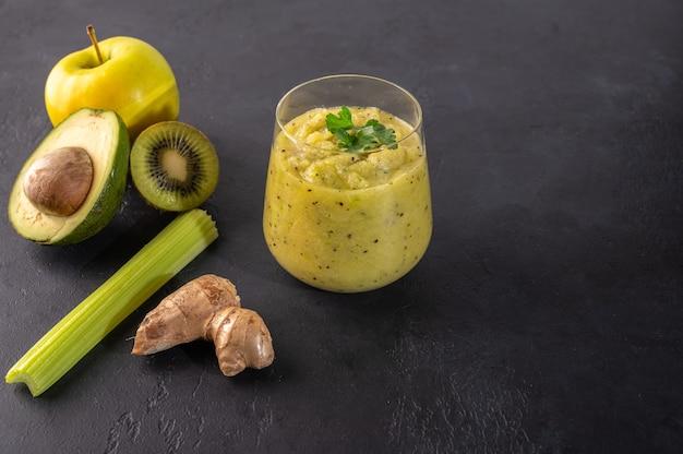 Frisch zubereiteter grüner smoothie aus ingwer, avocado, apfel, kiwi, sellerie, äpfeln, kräutern und gemüse