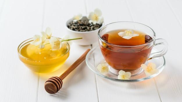 Frisch zubereiteter jasmintee mit jasminblüten und honig auf einem rustikalen weißen tisch.