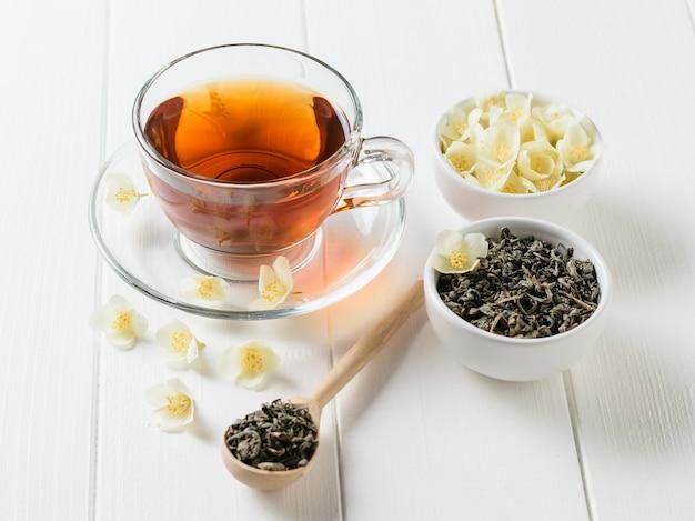 Frisch zubereiteter tee mit jasminblüten auf einem weißen holztisch