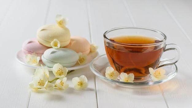 Frisch zubereiteter tee und bunte marshmallows auf einem weißen holztisch