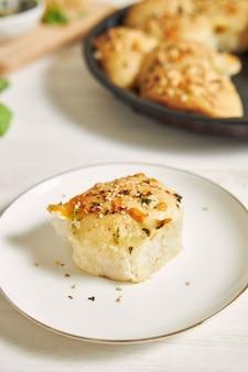 Frisch zubereitetes leckeres käse-blase-pizza-brot mit zutaten und käse auf einem weißen tisch
