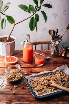 Frisch zubereitetes müsli auf backblech und grapefruitsaft auf küchentisch