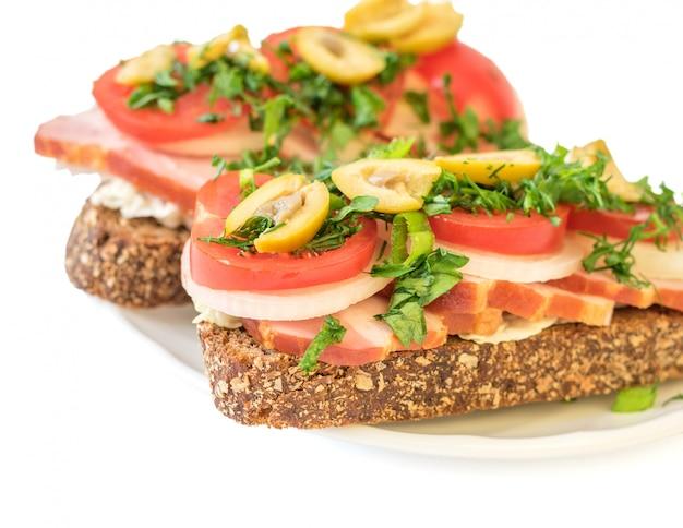Frisch zubereitetes sandwich mit schinken auf einer platte lokalisiert auf weißem hintergrund