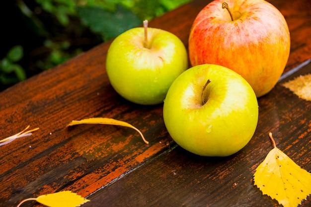 Frische äpfel auf einem nassen holztisch