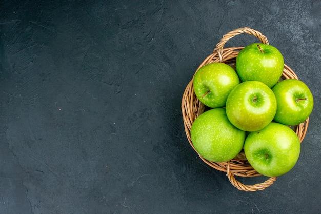 Frische äpfel der draufsicht im weidenkorb auf freiem raum der dunklen oberfläche