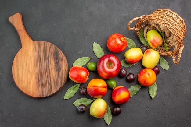 Frische äpfel der draufsicht mit pflaumen und pfirsichen auf dunklem reifem baum mildem vitamin
