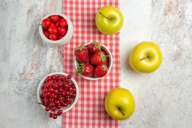 Frische äpfel der draufsicht mit roten beeren auf weißem tischobstbeerenfarbbaum