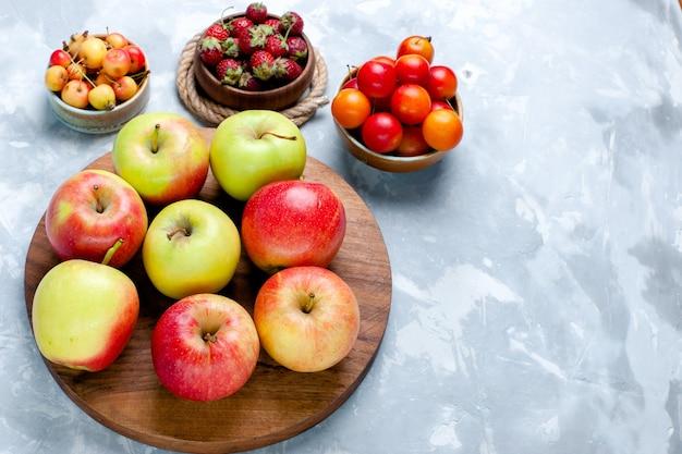 Frische äpfel der halben draufsicht reifen milden früchten auf dem hellen weißen schreibtischfruchtfutter-vitaminfarbenfrischbaum