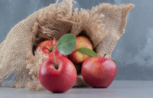 Frische äpfel, die aus einem mit stoff bedeckten korb auf marmor verschüttet werden.