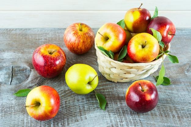 Frische äpfel im korb auf dem rustikalen hintergrund