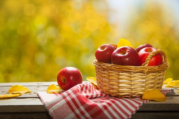 Frische äpfel im korb. auf hölzernem hintergrund. freier platz für text