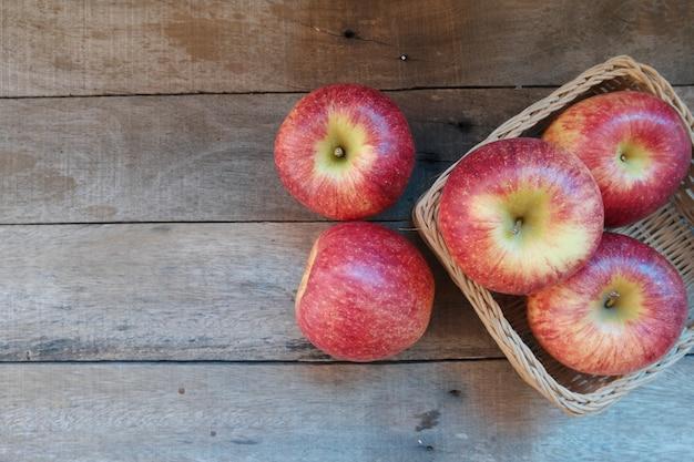 Frische äpfel im weidenkorb auf altem holz mit kopienraum
