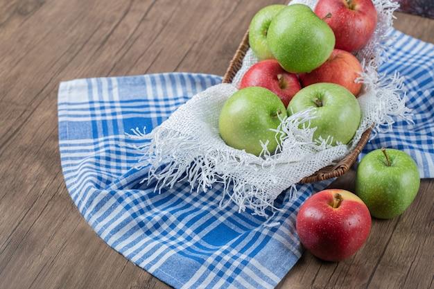 Frische äpfel in einem metallischen korb auf einem stück weißer leinwand.