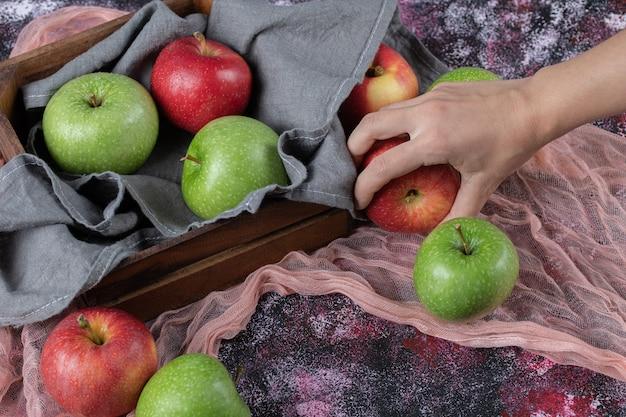 Frische äpfel in einem rustikalen holzbehälter.
