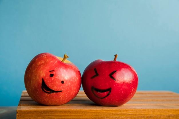 Frische äpfel mit lustigen gesichtern