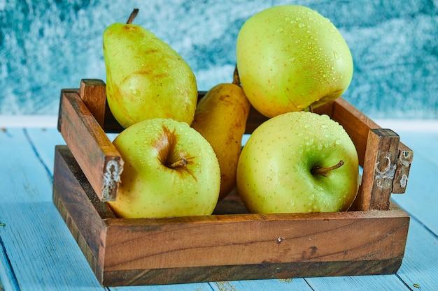 Frische äpfel und birnen in einer holzkiste auf blauer oberfläche. Kostenlose Fotos