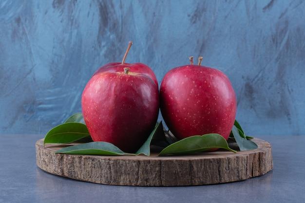Frische äpfel und blätter auf dem brett auf der dunklen oberfläche