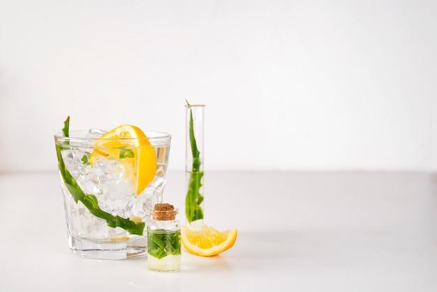Frische aloevera-blätter und aloevera-saft im glas auf weißem hintergrund