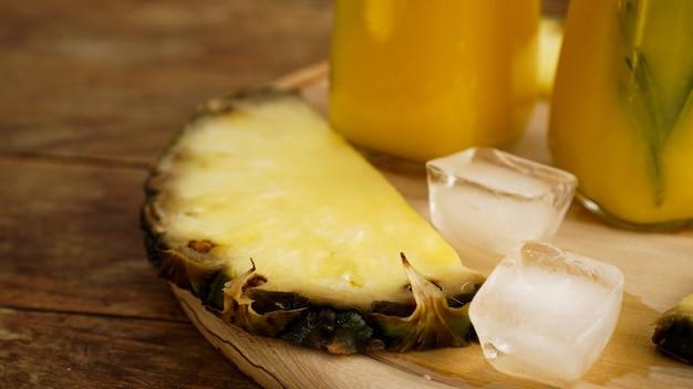 Frische ananasscheiben und eiswürfel auf einem hölzernen hintergrund. frischer ananassaft im hintergrund. kühlen sie an einem heißen sommertag. snack im resort