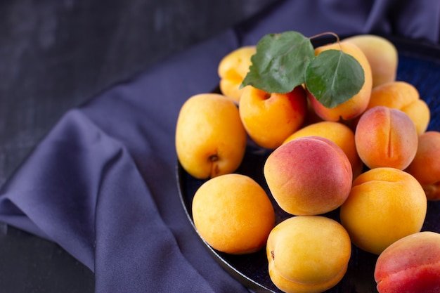 Frische aprikose auf dunklem seidenstoff