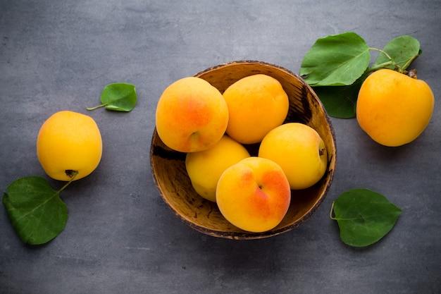 Frische aprikosen in der holzschale auf altem rustikalem hintergrund.