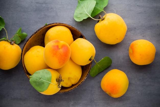 Frische aprikosen in der holzschale auf altem rustikalem tisch.