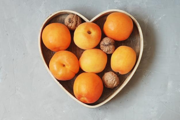 Frische aprikosenfrüchte in der geformten holzkiste des herzens.