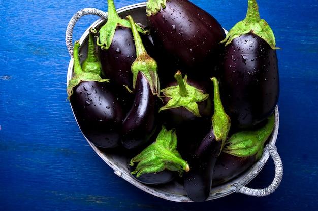 Frische aubergine im grauen korb auf blauem holztisch