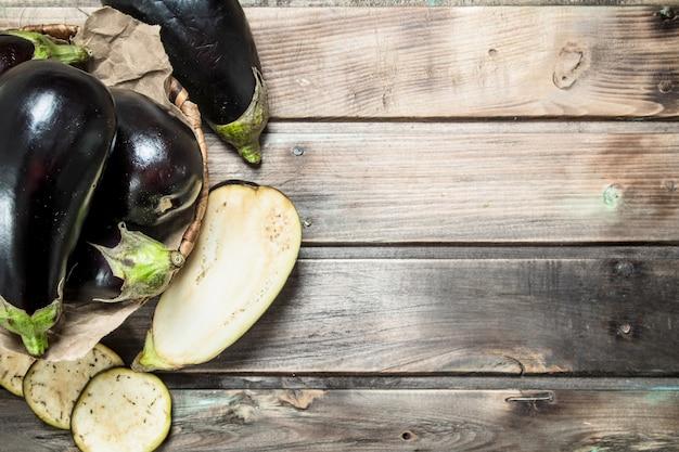 Frische aubergine im korb auf holztisch