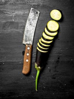 Frische auberginen mit einem alten messer und scheiben an der schwarzen tafel