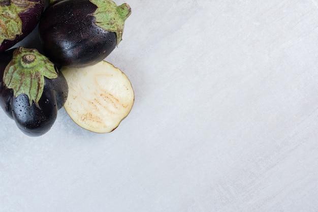 Frische auberginen mit wassertropfen auf steinoberfläche. hochwertiges foto