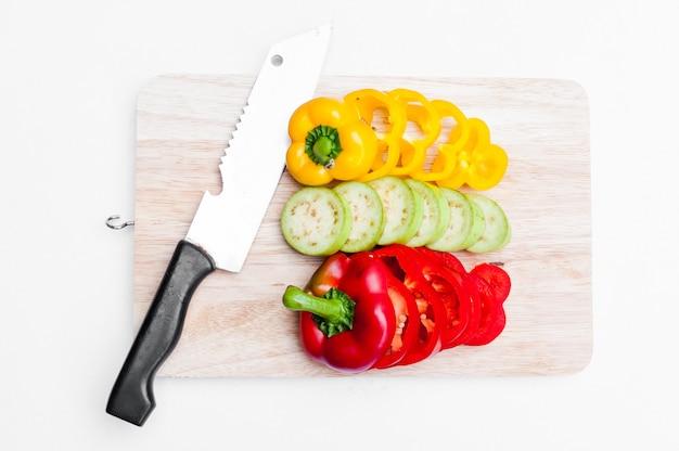 Frische auberginen und paprika gelb und rot auf holzbrett geschnitten