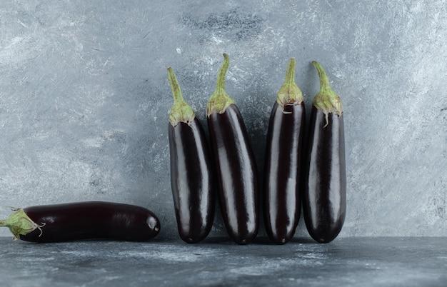 Frische auberginenreihe auf grauem hintergrund