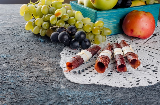 Frische ausgewählte äpfel und trauben und fruchtpastille auf dunkelheit