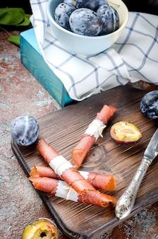Frische ausgewählte pflaumen in der tonwarenschüssel- und -pflaumenpastille auf dunklem hintergrund