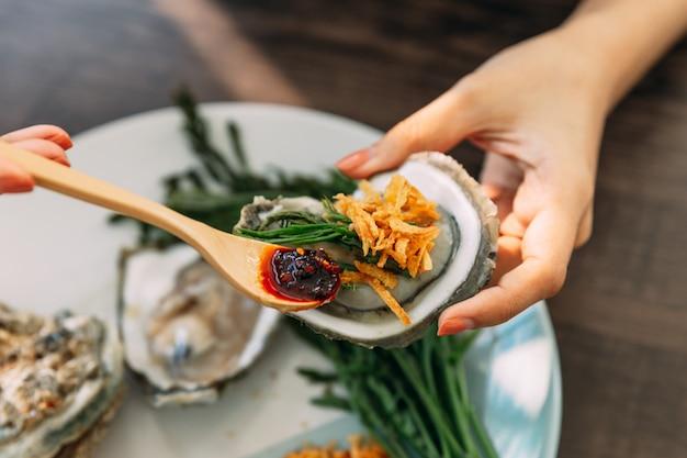 Frische auster in der schale in der hand, die mit gebratener schalotte, chilipaste, acacia pennata und meeresfrüchtesoße nach thailändischer art belegt.