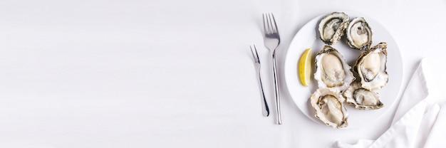 Frische austern dienten in der weißen platte mit geschnitten von der zitrone auf weißer tischdecke