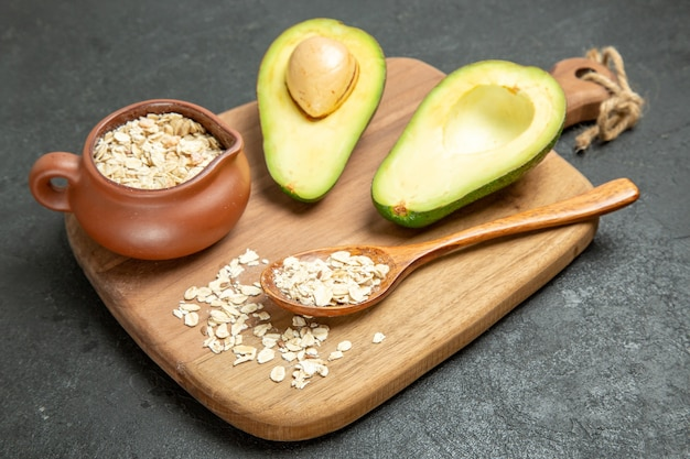 Frische avocado der vorderansicht mit rohem getreide auf dem exotischen frühstückfruchtfrisch des grauen hintergrundfruchtes frisch