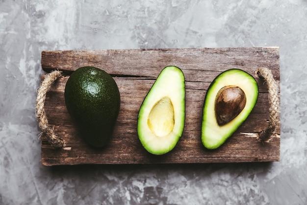 Frische avocado geschnitten über weinlesehintergrundhintergrundnahaufnahme. reife grüne avocadofrucht auf holzbrett.