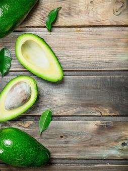 Frische avocado mit blättern. auf einem holz.