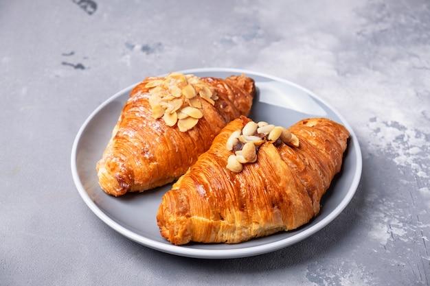 Frische backcroissants auf einem teller. croissants mit mandelflocken und nüssen.