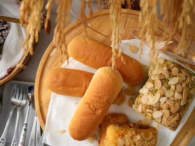 Frische backwaren in holztabletts und weizenkörnern auf einem tisch, weißes leinen