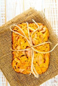 Frische bäckerei. draufsicht des gebackenen kuchens mit äpfeln auf sackleinen auf einem weißen holz. rustikaler stil.