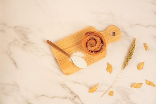 Frische bäckerei, frisches zimtbrötchen mit dem löffel voll vom mehl auf hölzernem brett auf weißer marmoroberfläche. leckeres leckeres dessert, französisches frühstück. ansicht von oben