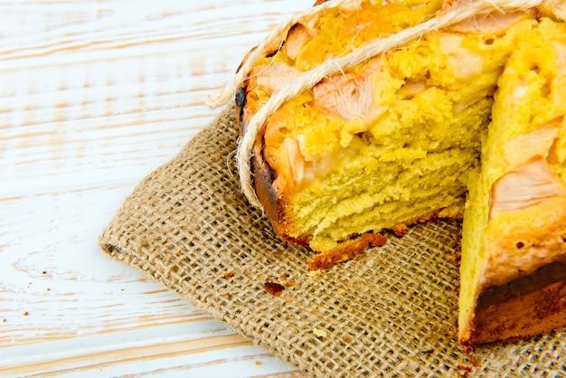 Frische bäckerei. nahaufnahme der gebackenen torte mit äpfeln auf sackleinen auf einem weißen holz. rustikaler stil.