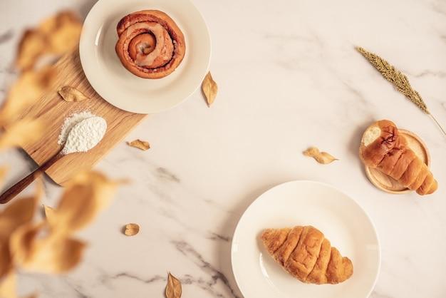 Frische bäckerei, zimtbrötchen und frisches hörnchen auf platte mit dem hölzernen löffel voll vom mehl auf hölzernem brett. geschmackvoller köstlicher nachtisch auf weißer marmoroberfläche. französisches frühstück. ansicht von oben