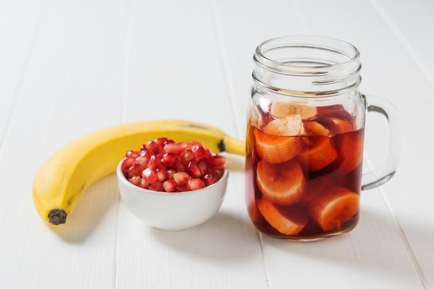 Frische banane, granatapfelkerne und granatapfelsaft in einem glasbecher. zutaten für die herstellung von granatapfel-smoothie.